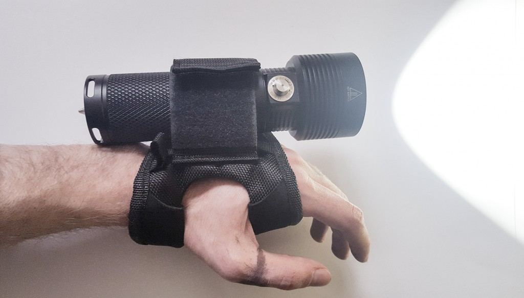 Включенный подводный фонарь Acebeam D400 закрепленный на руке пользователя